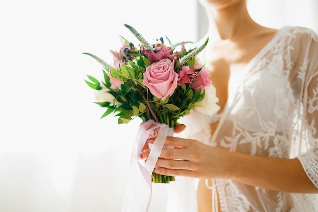 Een bruid in een witte kanten peignoir houdt een bruidsboeket in haar handen in een hotelkamer