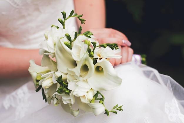 Een bruid in een witte trouwjurk houdt een bruidsboeket van witte calla lelies vast