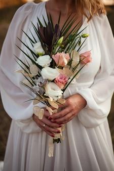 Een bruid in een witte trouwjurk houdt een delicaat bruidsboeket rozen en veel groen vast. stijlvol huwelijksboeket op een zonsondergangachtergrond