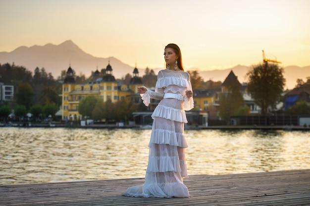 Een bruid in een witte trouwjurk in de oude binnenstad van oostenrijk bij zonsondergang