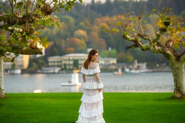 Een bruid in een witte trouwjurk in een park in een oostenrijks stadje met grote bomen bij zonsondergang. Premium Foto