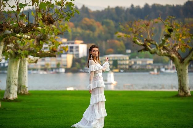 Een bruid in een witte trouwjurk in een park in een oostenrijks stadje met grote bomen bij zonsondergang.