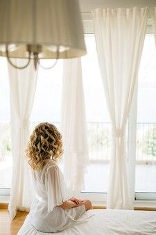 Een bruid in een zacht peignoir zittend op het bed bij het brede terrasraam met witte gordijnen