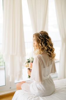 Een bruid in een zachte peignoir met een boeket in haar handen zittend op het bed bij het raam met wit