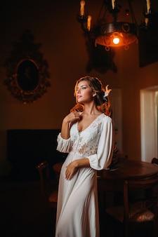 Een bruid in ondergoed en een wit gewaad in het interieur van een villa