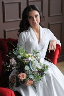 Een bruid in trouwjurk zittend op de rode bank met een bloemboeket