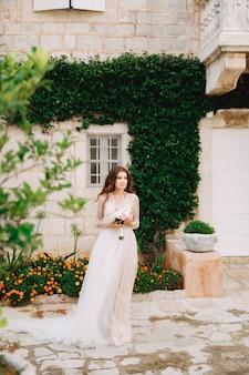 Een bruid met een boeket in haar handen staat aan de muur van een huis met een groene liaan en sinaasappel