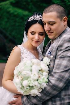 Een bruid met een tiara in een chique jurk en een bruidegom in een stijlvol pak in elkaars armen. bruid die wit huwelijksboeket houdt.