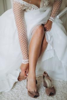 Een bruid om haar trouwschoenen aan te trekken. mooie vrouwelijke voeten close-up.