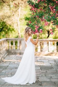 Een bruid op het terrein bij de oude kerk in prcanj, roze bloemen snuivend aan de weelderige takken van