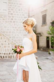 Een bruid staat in de straat van het oude centrum van perast, houdt een boeket in haar handen en glimlacht Premium Foto