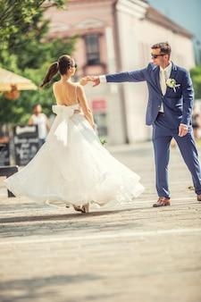 Een bruidegom danst met haar bruid in de stad na een bruiloft. nog steeds mooie gewaden aan en een boeket van witte bloemen vasthoudend.,