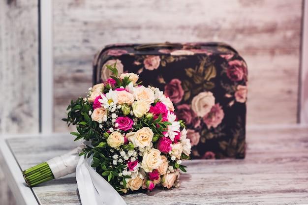 Een bruidsboeket ligt op een houten tafel naast een mooie koffer
