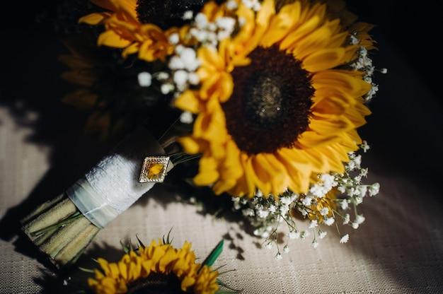 Een bruidsboeket met zonnebloemen ligt op een antieke stoel wedding decor