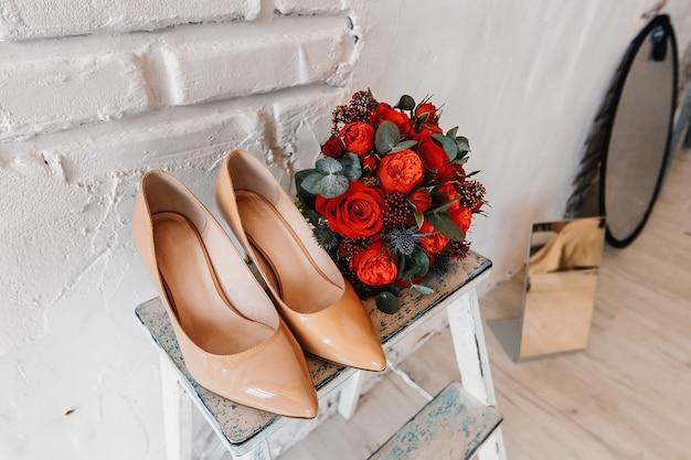 Een bruidsboeket van rode rozen en beige schoenen