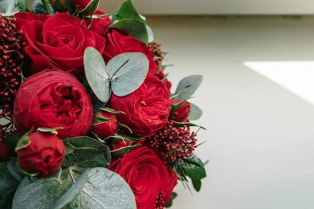Een bruidsboeket van rode rozen ligt