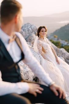 Een bruidspaar bovenop een berg in de baai van kotor, de bruid glimlacht naar de bruidegom bij zonsondergang. fine-art bestemming trouwfoto in montenegro, mount lovchen.