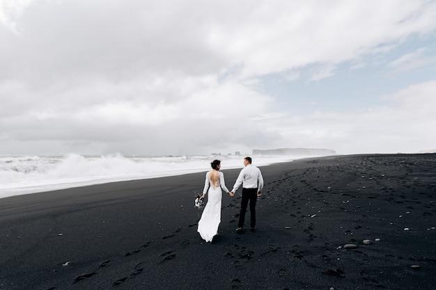 Een bruidspaar loopt langs het zwarte strand van vic
