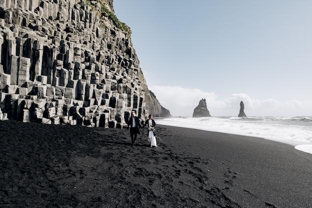 Een bruidspaar loopt langs het zwarte zandstrand van vik, vlakbij de