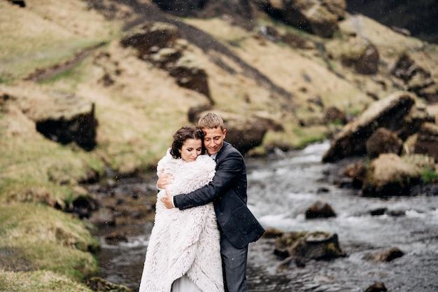 Een bruidspaar staat aan de oever van een bergrivier onder een wollen deken die de bruidegom de knuffelt