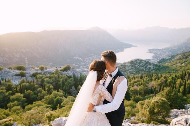 Een bruidspaar staat op de top van een berg met panoramisch uitzicht op de baai van kotor