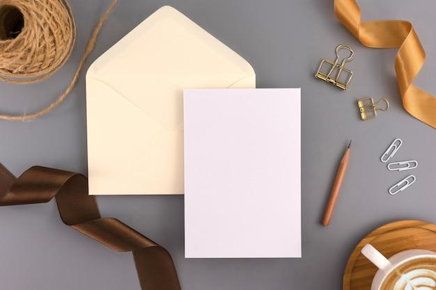 Een bruiloft concept. de kaart van de huwelijksuitnodiging op grijze achtergrond met lint en decoratie.