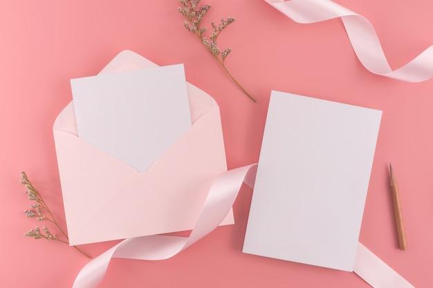 Een bruiloft concept. de kaart van de huwelijksuitnodiging op roze achtergrond met lint en decoratie.