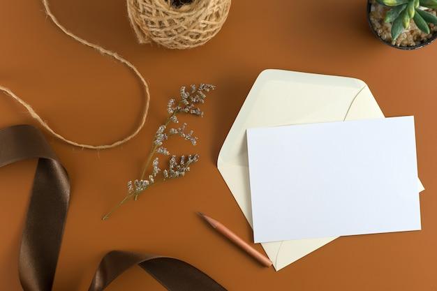 Een bruiloft concept. huwelijksuitnodiging op bruine achtergrond met lint.