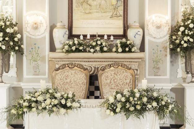 Een bruiloft tafel instelling met florale decoraties en kaarsen met hangende lampen