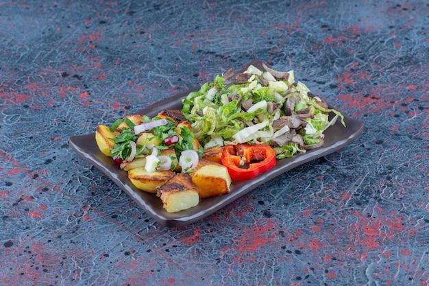 Een bruin bord groentesalade en gebakken aardappel.