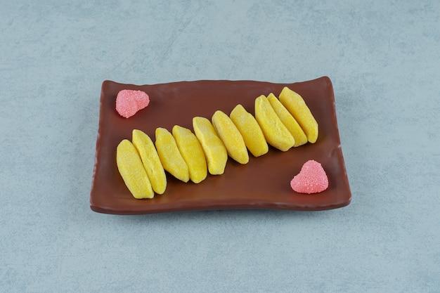 Een bruin bord met banaanvormige kauwsnoepjes met hartvormige zoete gelei-snoepjes