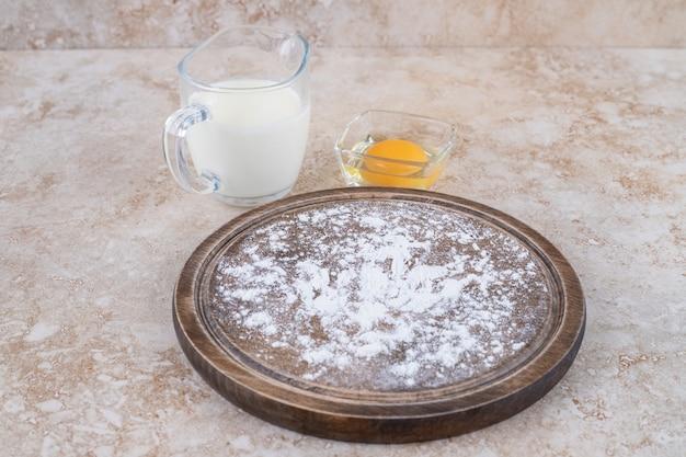 Een bruin bord met bloem en een glazen beker melk