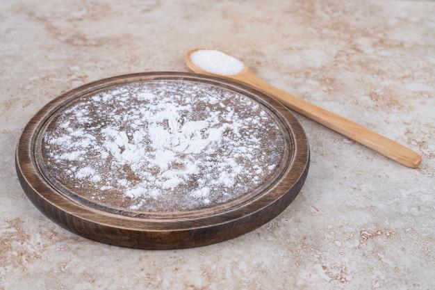 Een bruin bord met bloem en een houten lepel suiker