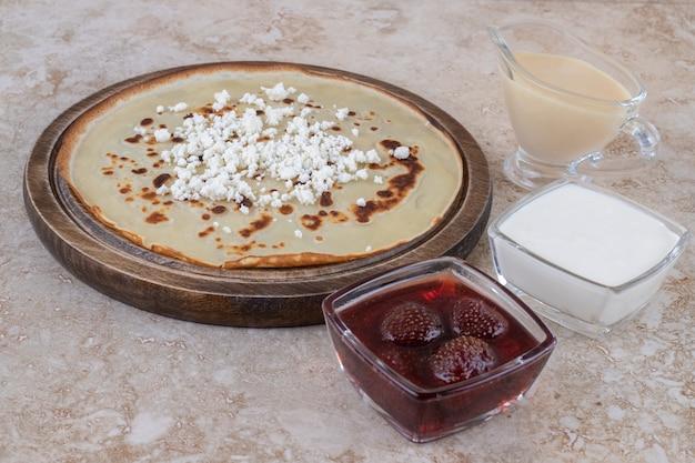 Een bruin bord met lekkere pannenkoeken en aardbeienjam