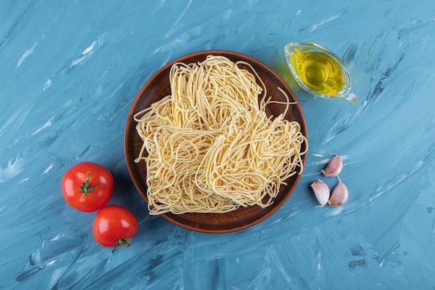 Een bruin bord rauwe noedels met twee verse rode tomaten en olie op een blauwe ondergrond.