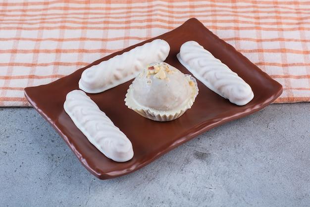 Een bruin bord van zoete witte stokjes met heerlijke cupcake.