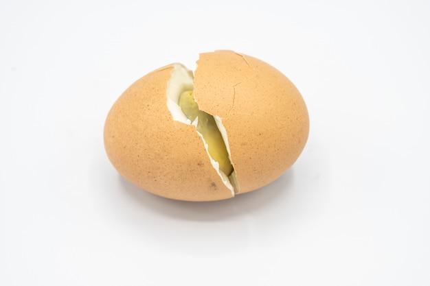 Één bruin ei en gekraakt op witte achtergrond
