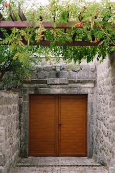 Een bruine houten ingang naar de binnenplaats met een baldakijn van gekrulde bloemen