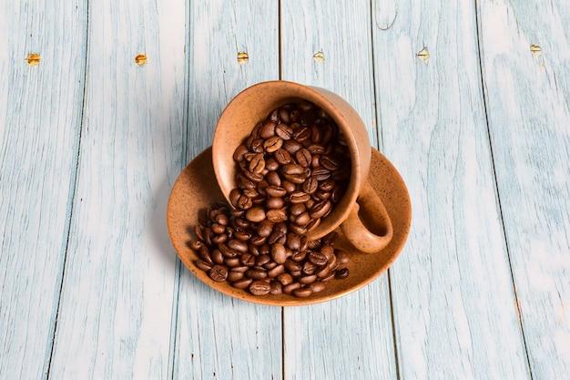 Een bruine keramische kop en schotel wordt omgedraaid en bestrooid met koffiebonen. een kopje staat in het midden van een blauwe houten achtergrond