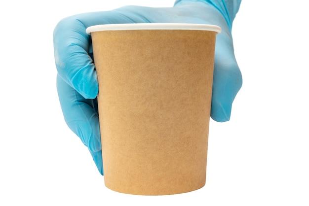 Een bruine papieren koffiekopje in een man hand in een blauwe medische handschoen