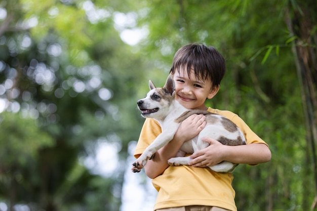 Een bruinharige jongen in een geel shirt draagt een puppy liefdevol in de tuin buiten.