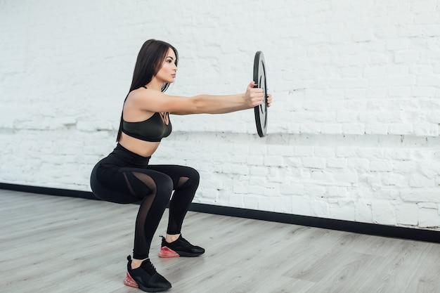 Een, brunette blanke vrouw die fitness oefeningen in de studio uitoefent. kopieer ruimte.