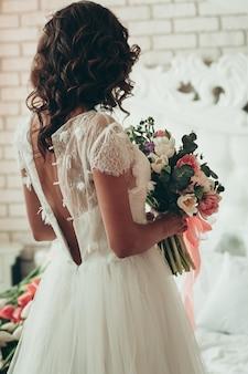 Een brunette bruid in losgeknoopte witte jurk met bruiloft boeket, achteraanzicht