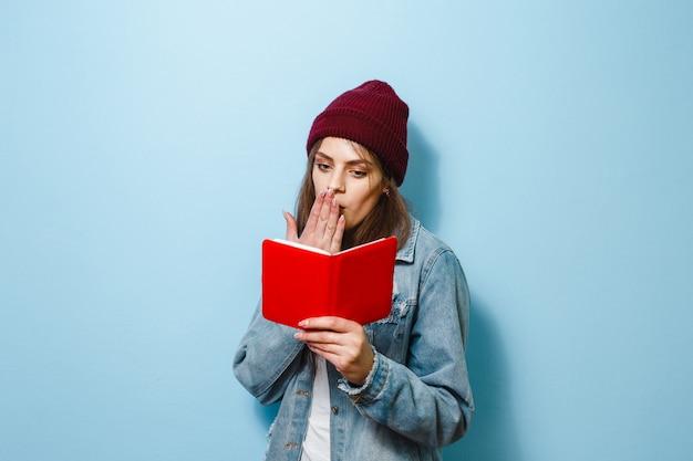 Een brunette meisje houdt haar gezicht met een boek