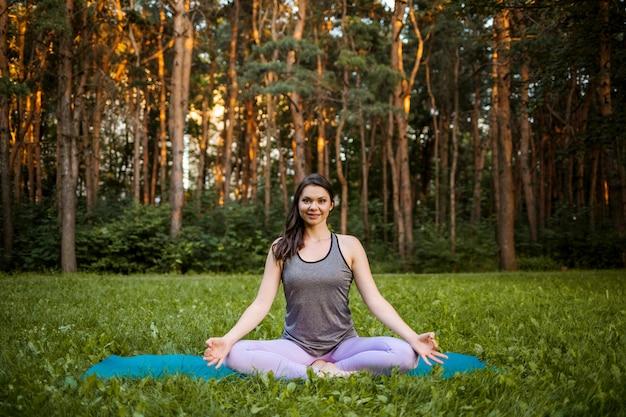 Een brunette meisje in een sport uniform voert de siddhasana asana in de natuur bij zonsondergang