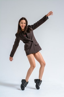 Een brunette meisje in een strikt bruin jasje en schoenen op een witte background.emotions van een zakenvrouw.