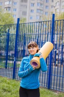 Een brunette meisje in sportkleding houdt een yogamat op haar schouder. een jong meisje in een blauwe colbert kijkt en glimlacht.