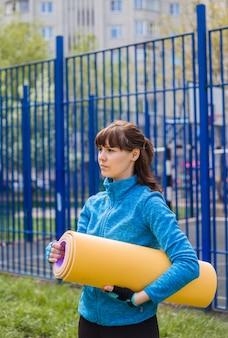 Een brunette meisje in sportkleding met een mat voor buitensporten. blauwe sportjas en gele yogamat.opzij kijken.gezonde levensstijl.