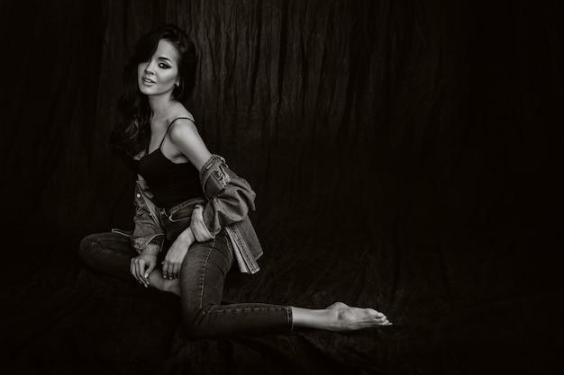 Een brunette met lang haar vormt in de studio zittend op de vloer op een zwarte achtergrond. zwart-wit foto.