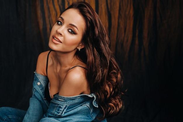 Een brunette met lang haar vormt in een studio zittend op de vloer op een zwarte achtergrond.